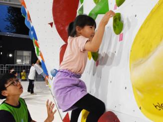 高校生から指導を受けボルダリングに挑戦する児童
