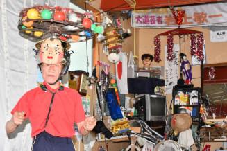 首や体幹の力で、器用に手作りの飾りを頭上でくるくる回す岩上敏一さん。高齢者施設慰問再開に向け大道芸を磨き続けている