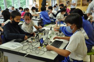 コンピューターにセンサーやモニターなどをつなぎ、プログラムを入力する児童
