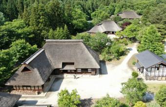 母屋と馬屋が一体となった伝統家屋「曲り家」=遠野市附馬牛町・遠野ふるさと村(本社小型無人機から撮影)
