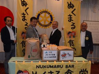阿部一郎会長(左から2人目)に食料を手渡す高橋利光専務(同3人目)