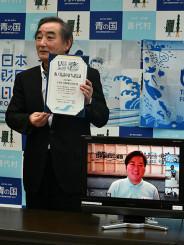 沼田心之介さんから画面越しに認定証を受け取った柾屋伸夫村長(左)