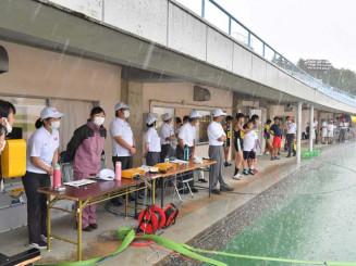 県中学校陸上大会の最中、突然の雷と大雨で避難する選手や関係者=19日午後2時23分、盛岡市みたけ・県営運動公園陸上競技場