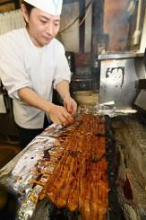 香ばしい匂いが漂う厨房で炭火焼きされるウナギ=20日、盛岡市大通・京極