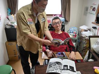 郷家準一さん(中央)と旅の同人誌を見る佐藤貴義さん。「(郷家さんは)大学が東京で、自分にとっては〝都〟の文化を持ち帰ってくれる存在だった」と語る=奥州市水沢・郷家さん宅
