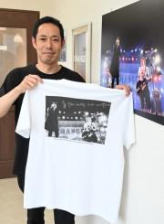 オリジナルTシャツを手に「音楽の喜びを共有できるように」と製作に込めた思いを語る黒沼亮介社長