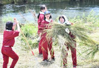 仲間と協力し合って草を運ぶ長内中の生徒