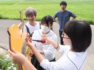 ひょうたん池までの順路を示す手作り看板を取り付ける平舘高美術部の生徒と斎藤学会長(左)ら