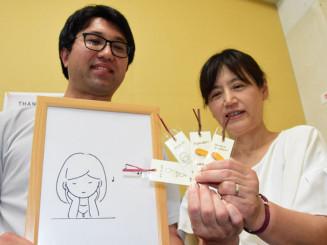 子どもたちを元気づけようと、しおりの配布に取り組むNPO法人未来図書館の田上孝幸さん(左)と恒川かおりさん