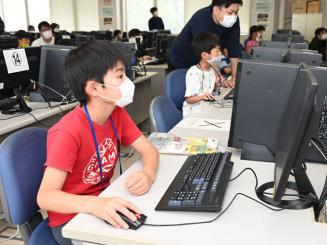 パソコン画面に集中しゲーム作成に取り組む小学生ら