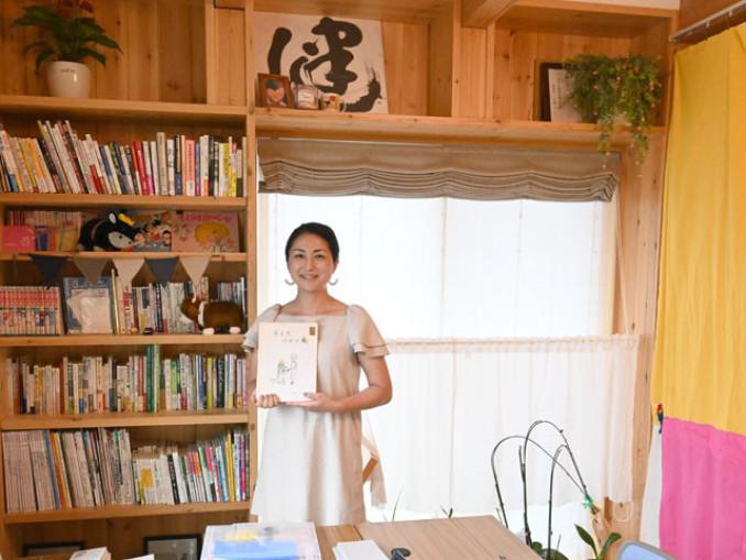 家庭文庫を開設した田村真由美さん。小学生の頃に自作した絵本を手に「家庭でも学校でもない第三の場所は大切」と説く