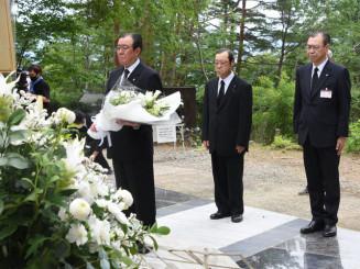 慰霊碑に献花する雫石町の猿子恵久町長(左)。大規模改修された現地で、地元関係者が空の安全を祈願した