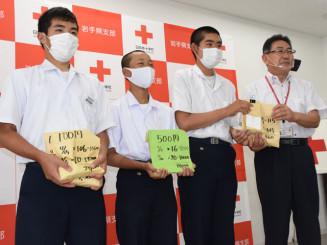 平野直事務局長(右)に義援金を手渡す滝沢南中の生徒