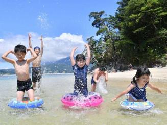 震災後初めて海開きが行われ、青空の下で元気に遊ぶ子どもたち=1日、山田町・オランダ島