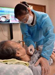 感染予防のためマスクや手袋を着用し、訪問先で利用者を検温する介護士。夏場は暑く、ゴーグルは曇る=盛岡市内
