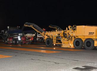 滑走路のアスファルト路面を削る重機=3日午後8時37分、花巻空港