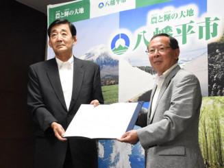 協定を取り交わす田村正彦市長(右)と高橋三男会長