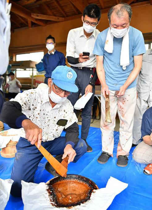 初出荷式で木べらを使い漆の状態を確かめる工藤竹夫さん(左)ら=二戸市浄法寺町