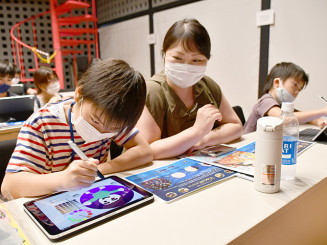 タブレット端末に思い思いの絵を描きながらプログラミング技術を学ぶ児童ら