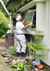 クマに割られた窓ガラスを交換する業者。地面には台所用品が散乱している=6日、釜石市甲子町