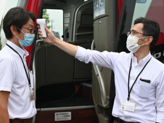 非接触型体温計による体温チェックを紹介するバス会社の社員=盛岡市