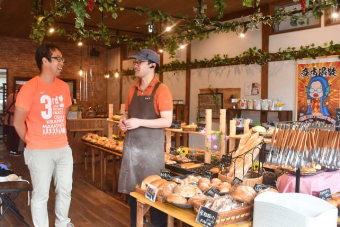 「パン工房くろしぇっと」で鈴木希店主(右)とパン作りのアイデアを語り合う佐藤幸治さん