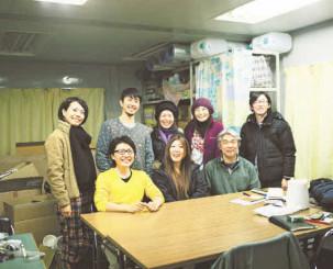 被災写真の返却ボランティアと写真に納まる浅田政志さん(後列左から2人目)。自身の作品が原案となった映画が震災の現実を伝え、風化を防ぐきっかけとなることを願う=2012年1月((c)浅田政志)