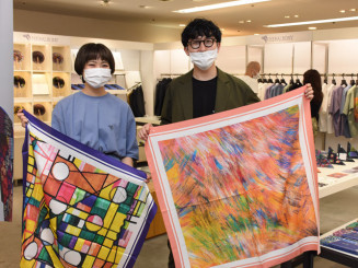 知的障害のあるアーティストが描いた作品を手に魅力を伝える深沢佳歩さん(左)と松田文登副社長