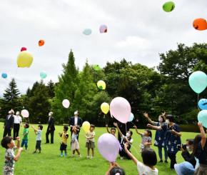 風船を一斉に空に放ち、来年のトリプルアニバーサリーの盛り上がりを願う黒沢尻幼稚園の園児ら