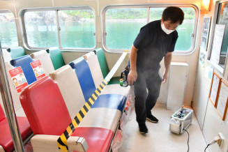 特殊な薬剤を噴霧する機械(右下)で遊覧船の客室内を抗菌化する作業員