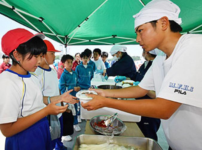 作ったカレーを藤原小児童と河南中の生徒に手渡す宮古水産高の生徒(右)