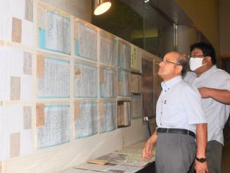 戦地から家族へ送られた手紙を見つめ、平和の大切さをかみしめる鈴木公男会長(左)