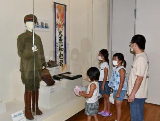 戦没者の遺留品を見て、平和の尊さをかみしめる家族連れ