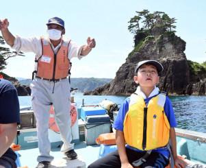 サッパ船で海岸線を巡り、船長の解説に耳を傾ける子ども