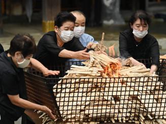戦没者の名前が記された火たき串を火にくべる参列者=15日、盛岡市八幡町・岩手護国神社