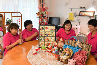 手作りの作品を囲み談笑する伊藤百合子さん(左から2人目)ら