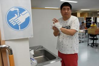 手洗いを促す絵カードを見て手を洗う施設利用者。感染症の拡大を防ぐため衛生習慣の定着を視覚的に訴える=花巻市石鳥谷町