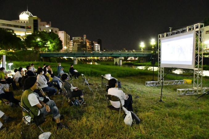 中津川沿いで今月上旬開かれた野外上映会。夜風を感じながらの観賞は好評だった=盛岡市