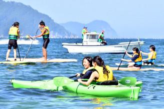 カヌーやSUPなどマリンスポーツを満喫する山田中生=20日、山田町船越・浦の浜海水浴場