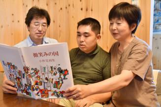 小林覚さん(中央)の初めての画集を眺める父俊輔さんと母真喜子さん。ずっとそばで寄り添ってきた
