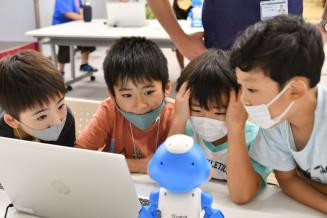 作成したプログラム通りに動くロボットに興味津々の子どもたち