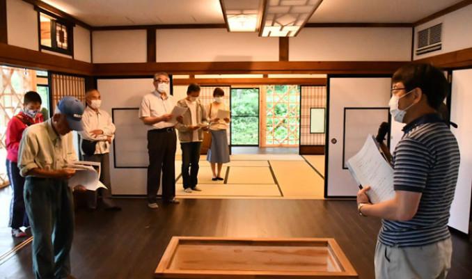 工藤光幸課長(右)から施設の説明を受ける見学者