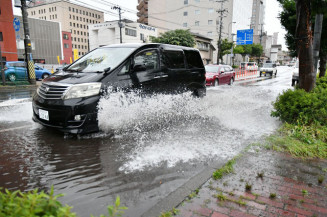 水しぶきを上げて市道を走行する車=30日午後4時ごろ、盛岡市盛岡駅前通