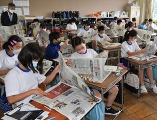 紙面を開き、見出しや記事に目を通す大慈寺小5年生