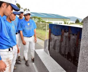 学校に戻ってきた記念碑を前に甲子園出場への誓いを新たにする高田高野球部員=陸前高田市高田町