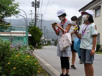 民家の庭先の花に着目してシャッターを切る児童