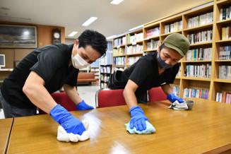 生徒が安心して過ごせるよう入念に塗布する岩下一樹社長(右)