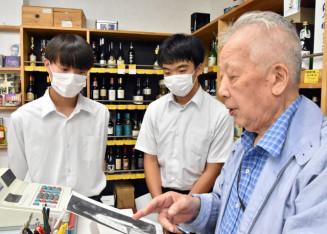 佐野健司さん(右)の話に聞き入る太田堅さん(左)と杉田翔さん=釜石市大町