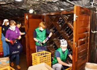 龍泉洞の貯蔵庫で熟成させた日本酒を取り出す社員ら
