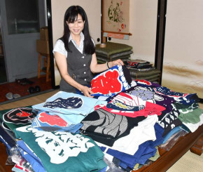 町内会や企業などから提供されたはんてんを見つめる伊藤純子社長